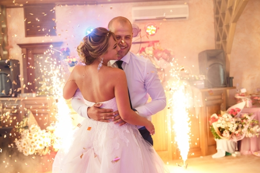 Wedding dance of bride and groom with special effects- colorful smoke and fireworks. Newlyweds couple dancing at wedding day. Marriage and wedding party concept